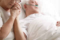 stock image of  senior man in hospital bed and his wife holding his hand