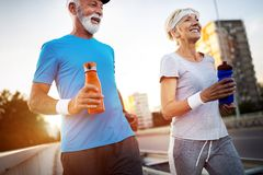 stock image of  senior woman and man running doing fitness exercises