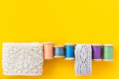 stock image of  sewing crafts hobbies fashion clothing background with white cotton lace rolls wooden vintage spools with multicolored threads