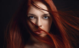stock image of  beautiful redhead girl with long hair. perfect woman portrait on black background. gorgeous hair and deep eyes natural beauty
