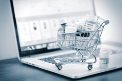 stock image of  shopping cart full of homeopathic remedies on laptop