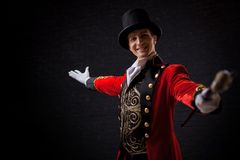 stock image of  showman. young male entertainer, presenter or actor on stage. the guy in the red camisole and the cylinder.