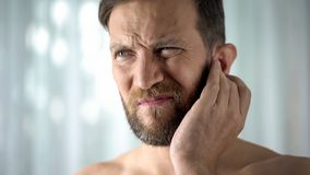 stock image of  sick guy feeling ear pain, health care, neurological infection, itchiness otitis