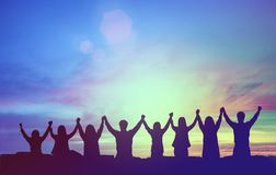 stock image of  silhouette of happy teamwork hold hands up as a business successful, victory. business goal achievement, hit company target.
