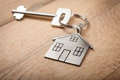 stock image of  close up silver home shaped keychain with key on wooden background. mortgage, investment, real estate, property and new home conce