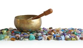 stock image of  singing bowl resting on bed of tumbled healing stones