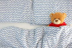 stock image of  single brown bear doll wear red shirt sleeping on the bed have space on the left side. concept waiting for someone to sleep with h