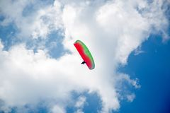 stock image of  skydiver on colorful parachute in blue sky. active hobbies