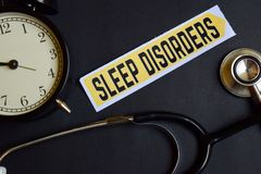 stock image of  sleep disorders on the paper with healthcare concept inspiration. alarm clock, black stethoscope.