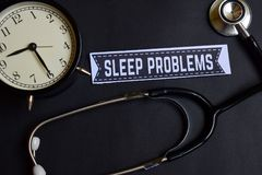 stock image of  sleep problems on the paper with healthcare concept inspiration. alarm clock, black stethoscope.