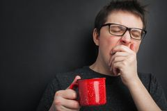 stock image of  sleepy yawning man in eyeglasses with red cup of tea or coffee has uncombed hair in underwear on black background, morning refresh