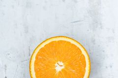 stock image of  slice of ripe juicy vibrant vivid color orange on gray stone concrete metal background. high resolution food poster. vitamins
