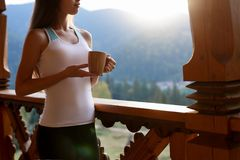 stock image of  slim caucasian woman holds cup of tea in her hands at mountain resort. sports girl with hot coffee mug at wooden balcony