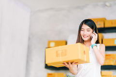 stock image of  small business owner, asian woman hold package box, using mobile phone call receiving purchase order, working at home office