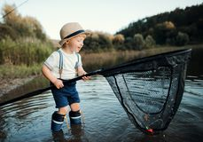 stock image of  a small toddler boy standing in water and holding a net by a lake, fishing.
