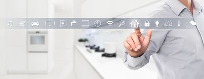 stock image of  smart home automation control hand touch screen with white symbols on kitchen background web banner and copy space template
