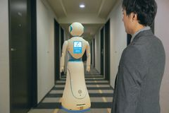 stock image of  smart hotel in hospitality industry 4.0 technology concept, robot butler robot assistant use for greet arriving guests, deliver cu