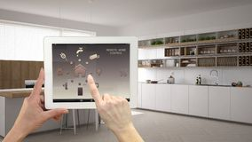 stock image of  smart remote home control system on a digital tablet. device with app icons. interior of minimalist white kitchen in the backgroun