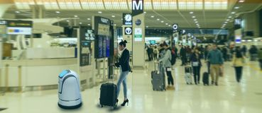 stock image of  smart robotic technology concept, the passenger follow a service robot to a counter check in in airport, the robot can help and gi