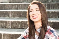 stock image of  smiling beautiful female enjoying freetime and posing outside