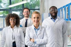stock image of  smiling group of scientists in modern laboratory with female leader, mix race team of scientific researchers in lab
