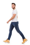 stock image of  smiling man in jeans and white t-shirt is walking side view