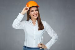 stock image of  smiling woman engineer builder worker touching her protect helmet.