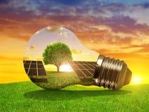 stock image of  solar energy panels in light bulb at sunset.