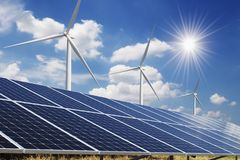 stock image of  solar panel and wind turbine blue sky with sun background. concept clean power