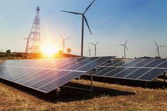 stock image of  solar panel with wind turbine and sunlight. clean power energy c