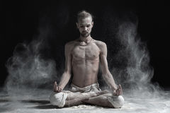 stock image of  sporty serene young man meditating sitting in cross-legged yoga lotus pose, padmasana with palms in mudra