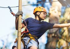 stock image of  sporty, young, cute boy in white t shirt spends his time in adventure rope park in helmet and safe equipment in the park