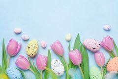 stock image of  spring composition with pink tulip, colorful eggs and feathers on blue table top view. happy easter card.