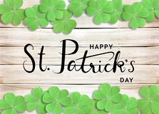 stock image of  happy st. patrick`s day black text typography background with green shamrocks on wooden texture