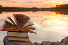 stock image of  stack of book and open hardback book on blurred nature landscape backdrop against sunset sky with back light. copy space, back to