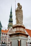 stock image of  the statue of knight roland, the recognizable and famous symbol of the town hall square on the background of the facade