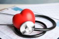 stock image of  stethoscope, red heart and cardiogram on table.