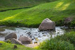 stock image of  stones in the river interfere with the flow of water, the lawn by the river