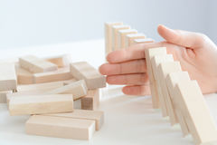 stock image of  stopping the domino effect concept with a business solution and intervention