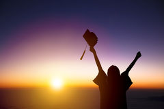stock image of  student celebrating graduation watching the sunlight