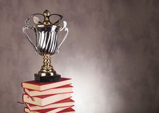 stock image of  student champion award with glasses on pile of books