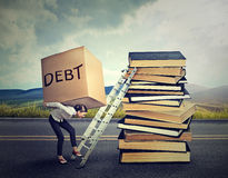 stock image of  student loan debt. woman with heavy box debt carrying it up education ladder