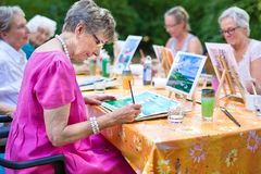 stock image of  stylish senior lady painting in art class with friends from her care home for the aged copying a painting with water colors.