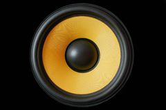 stock image of  subwoofer dynamic membrane or sound speaker isolated on black background, yellow hi-fi loudspeaker close up