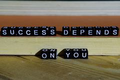 stock image of  succes depends on you on wooden blocks. motivation and inspiration concept