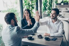 stock image of  success and agreement between three business partners, they celebrate sitting in cafe, wearing suits, smiling. terrace is