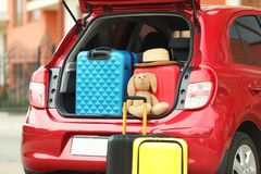 stock image of  suitcases, toy and hat in car trunk
