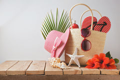 stock image of  summer beach bag and hibiscus flowers on wooden table. summer holiday vacation concept. view from above