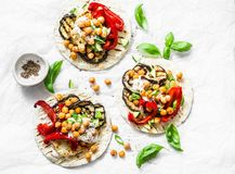 stock image of  summer grilled garden vegetables and spicy chickpeas vegetarian tortillas on a light background, top view. healthy food