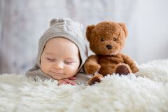 stock image of  sweet baby boy in bear overall, sleeping in bed with teddy bear